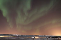 Aurora borealis over Kuparuk River Unit flowlines; glow on horizon from drillsites and Kuparuk Operations Center