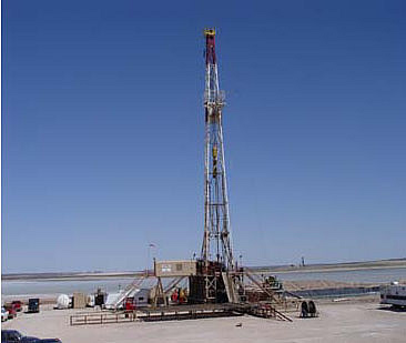 Drilling the Nash #34 well on the edge of the playa lake with a potash mine shaft in the background.