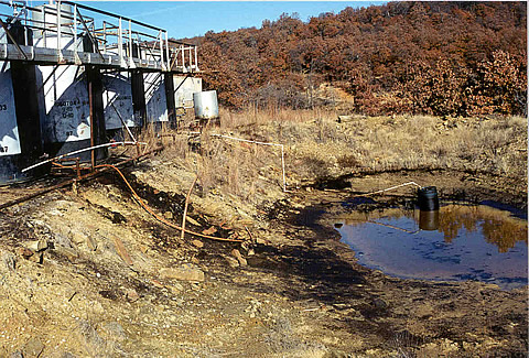 A tank battery showing produced water discharged to a holding pond in Osage County, OK. The fate of trace hydrocarbons, which leak from such holding ponds, was the focus of the research.