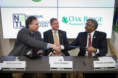 Assistant Secretary for Fossil Energy Steve Winberg looks on as Acting NETL Director Sean Plasynski (left) and ORNL Director Thomas Zacharia shake hands.